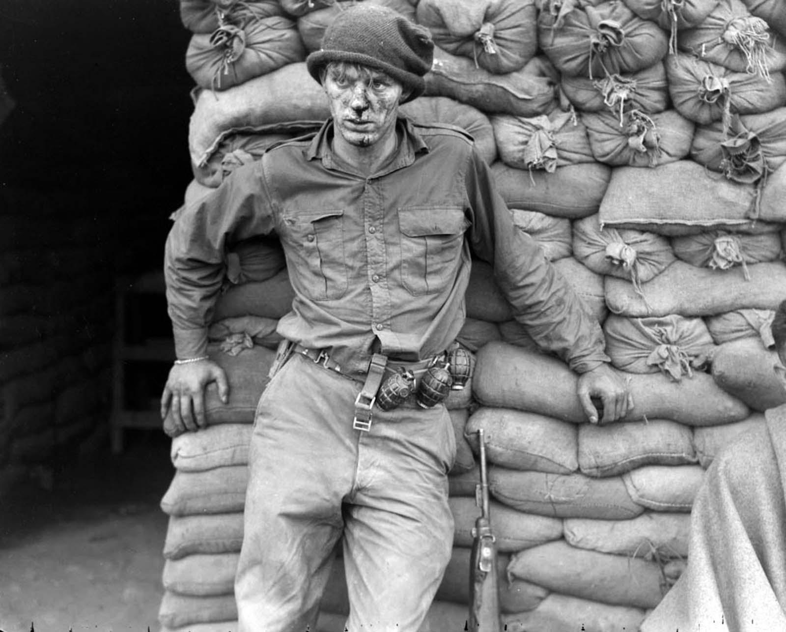 Privé Heath Matthews d'attente pour les soins médicaux à la suite d'un raid sur des positions ennemies pendant la Guerre de corée, 1952