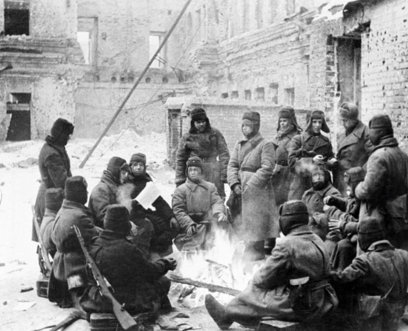 Hommes de l'armée rouge sont chauffés par le feu dans la rue de Stalingrad