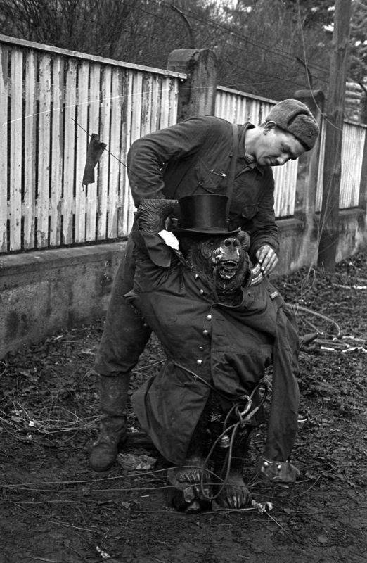 Un combattant de l'armée rouge essayage d'un uniforme allemand et le cylindre de la sculpture d'ours dans la rue de Berlin. Mai 1945