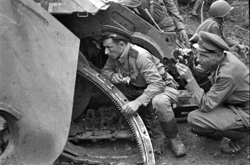 Les militaires soviétiques photographes mènent la prise de vue, se cachant derrière brisé d'un char allemand. Avril-mai 1943