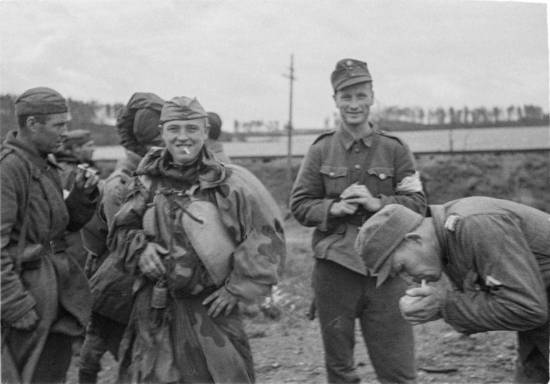 Des soldats soviétiques et finlandais fument sur la ligne de contact sur l'île de Sorvali à Vyborg. 4 septembre 1944