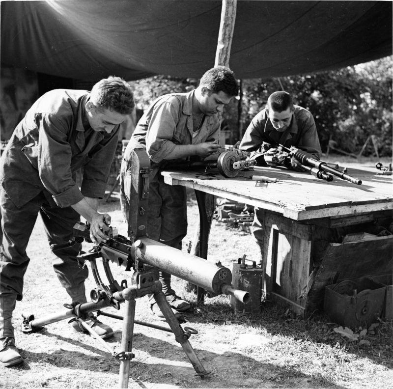 Armuriers d'une des unités américaines inspectant les armes capturées en Normandie. Juin-août 1944