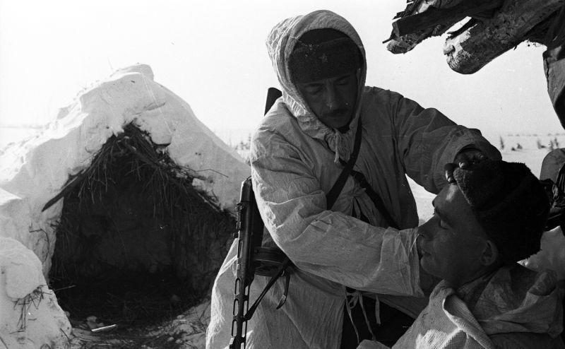 Scout soviétique rase un camarade dans le village près d'un abri fait de branches et de neige
