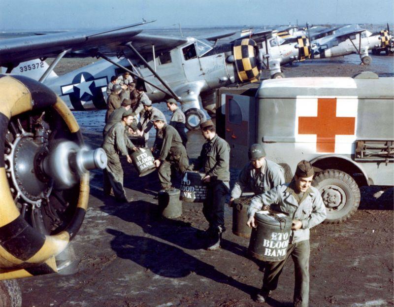 Des soldats américains déchargent des conteneurs de sang d'un avion UC-64 en Normandie. 1944 g.