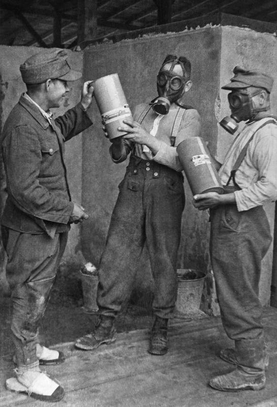 Les bourreaux du camp de concentration de Majdanek dans des masques à gaz avec des conteneurs de gaz toxique Cyclone-B. Juillet 1944