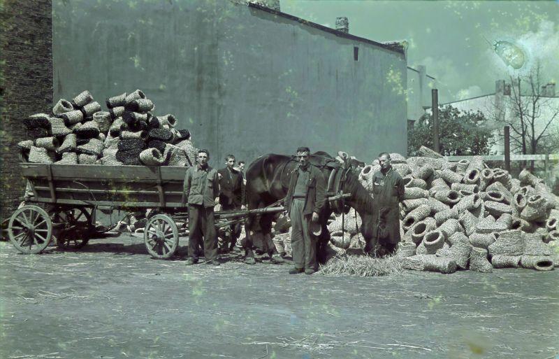 Les travailleurs du ghetto de Lodz par un chariot avec des bottes de protection en paille. 1942 g.