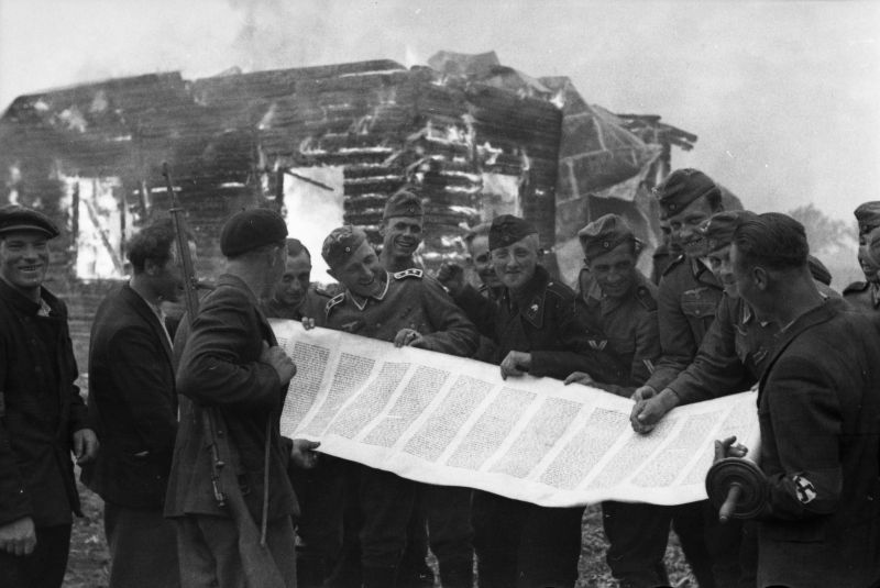 Les soldats de la Wehrmacht et la police lituanienne avec un rouleau de la Torah devant une synagogue en feu. Juin 1941