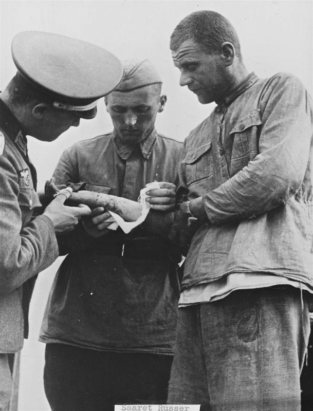 Un médecin allemand, avec l'aide d'un ambulancier soviétique capturé, examine la blessure d'un soldat de l'Armée rouge. Juillet 1941