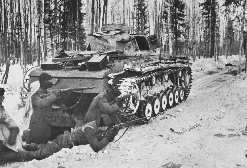 Des soldats SS au combat sous le couvert d'un Pz.Kpfw. III sur le territoire de l'URSS. Mars 1942