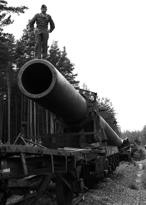 """Un officier américain se tient sur le canon d'un canon de chemin de fer allemand """"Fat Gustav"""". 1945 g."""