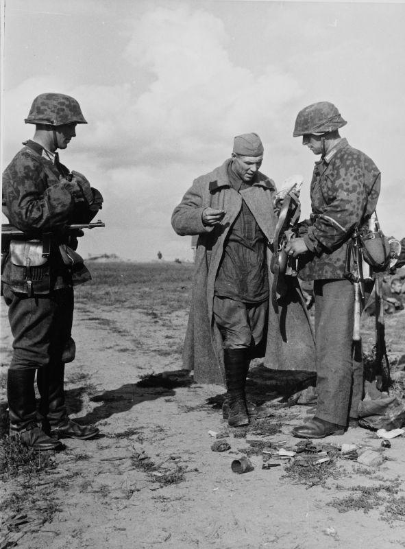 Des soldats de la division de police allemande fouillent un soldat de l'Armée rouge capturé dans la région de Luga. Août - septembre 1941