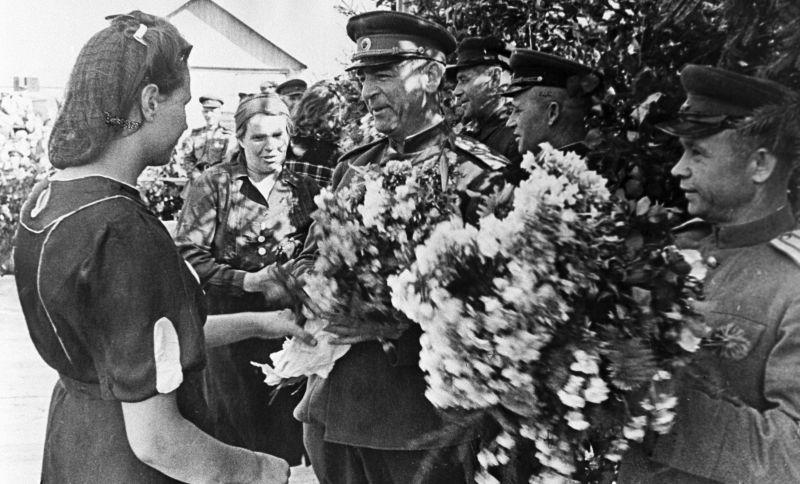 Les habitants du village letton libéré offrent des fleurs au lieutenant-général V.N. Bogatkin. Août 1944