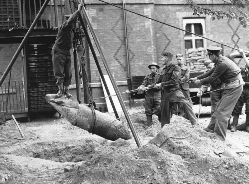 Le lieutenant R. Davis se dresse sur une bombe allemande non explosée lors de sa montée à Londres. 20 septembre 1940
