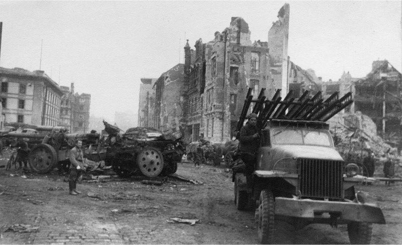 Le MLRS BM-13-16 soviétique passe à Berlin devant un obusier allemand de 150 mm cassé SfH 18. Avril 1945